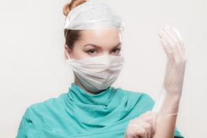cna with protective gloves, mask and apron